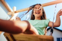 Low angle view of a little girl wearing green shirt sitting on the swing at backyard playground