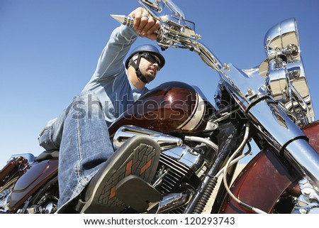 Low angle view of a man riding motorcycle against clear sky