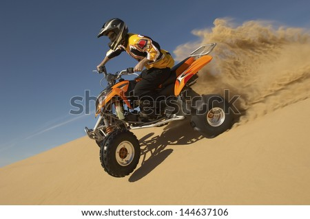 Low angle view of a man riding quad bike in desert against the blue sky Stock photo ©