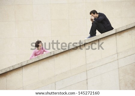 Low angle view of a man taking photograph of woman on stairway