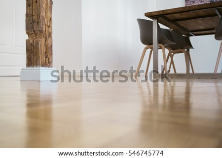 Low angle view of a rustic pillar architectural feature in the dining area of a home viewed across the parquet floor