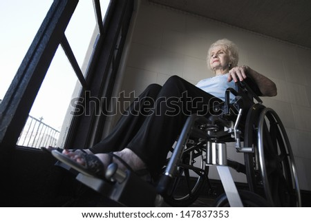 Low angle view of a senior woman in wheelchair - stock photo