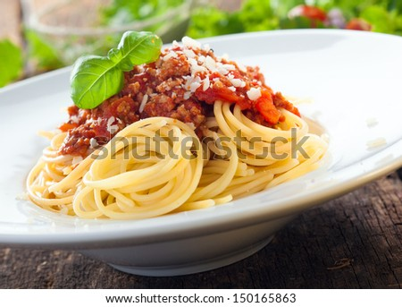 Low angle view of a serving of Italian spaghetti with a meat based bolognese, or bolognaise, sauce on a plain white plate