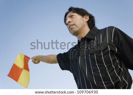 Low angle view of a soccer referee showing offside flag