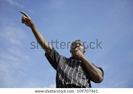 Low angle view of a soccer referee whistling while pointing to a player