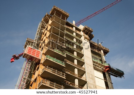 Low-angle view of a tall commercial building under construction against a blue sky. Horizontal format.
