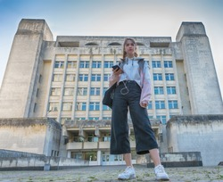 Low angle view of a trendy young college student with a bag of books over her shoulder and mobile phone in her hand standing outside a high-rise office block looking away as she listens to her music