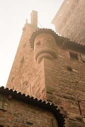 Low angle view of a watchtower of Haut-Koenigsbourg castle in the mist in winter, Alsace, France