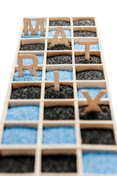 Low angle view of a wooden box with square compartments rectangular compartments filled with blue or black decorative sand and the letters M, A, T, R, I and X vertical in the sand.