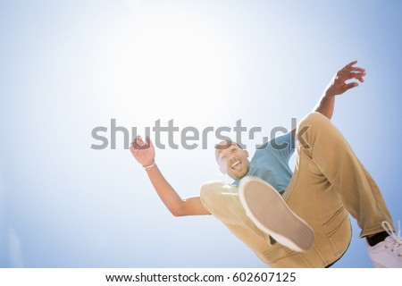Photo of Low angle view of a young man jumping in the air