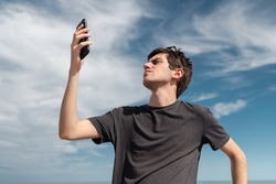Low angle view of a young man searching for signal on his smartphone. Concept of connectivity and connection problems.