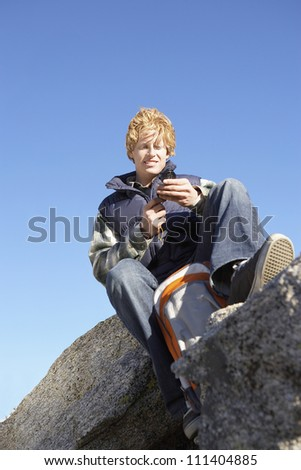 Low angle view of a young man with compass sitting on a rock