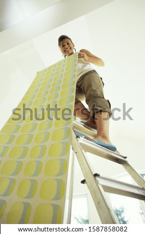 Low angle view of a young woman unrolling wallpaper Stockfoto ©
