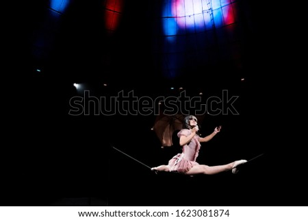 low angle view of aerial acrobat in costume holding umbrella and doing splits on rope