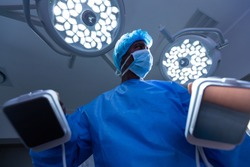 Low angle view of African-american male surgeon using defibrillator while looking away in operating room at hospital. Shot in real medical hospital with doctors nurses and surgeons in authentic