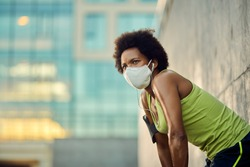 Low angle view of African American sportswoman taking a break after running with protective face mask in the city. Copy space.