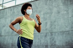 Low angle view of African American sportswoman with protective face mask running in the city. Copy space.