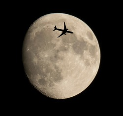 Low Angle View Of Airplane Flying By Moon Against Clear Sky At Night. Silhouette of plane passing over super moon.