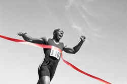 Low angle view of an African American male runner crossing finish line against blue sky