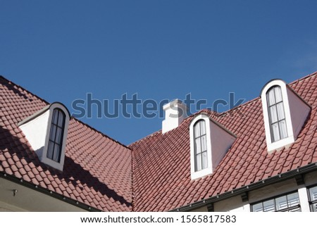 Low angle view of an angled red tile roof with tall slim dormer windows under a bright blue sky