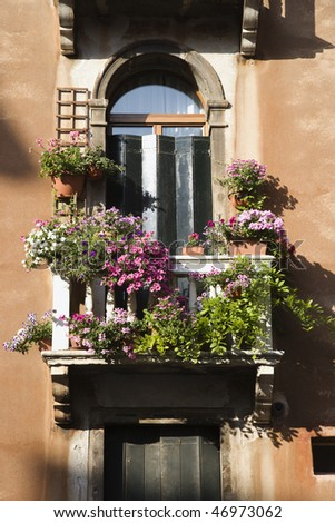 Low angle view of arched window with balcony and flowers in Venice, Italy. Vertical shot. - stock photo