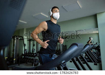 Low angle view of athletic man wearing protective face mask while running on treadmill in a gym.
