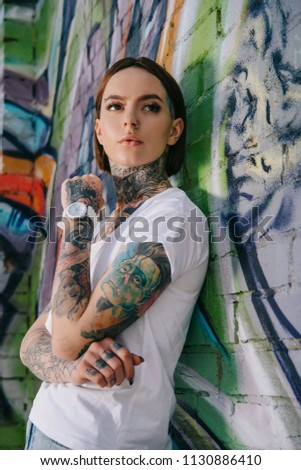 Stock Photo low angle view of attractive young tattooed woman posing near wall with graffiti