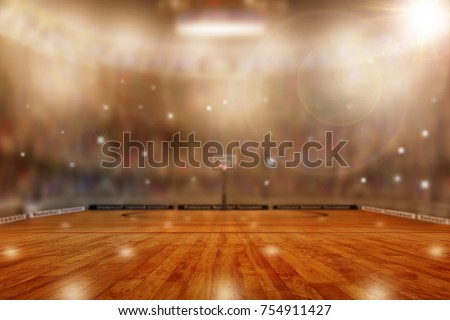Low angle view of basketball arena with flashes from sports fans in the stands and lens flare effect. Focus on foreground with deliberate shallow depth of field on background and copy space.