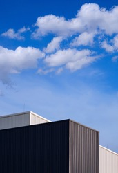 Low angle view of black and white corrugated metal factory buildings against clouds and blue sky background in vertical frame