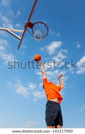 Low angle view of boy playing basketball against blue sky