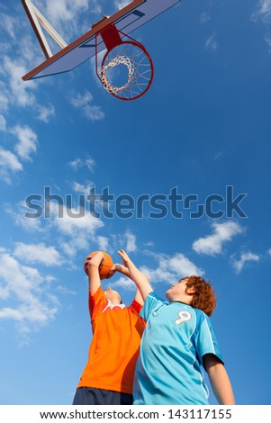 Low angle view of boys playing basketball against sky