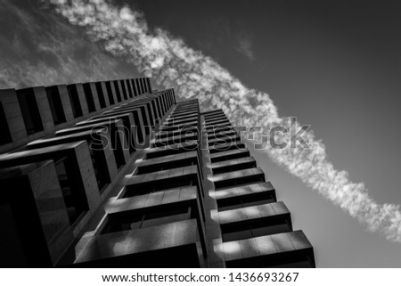 Low Angle View of Building with Sharp Angles Against Contrails in the Sky