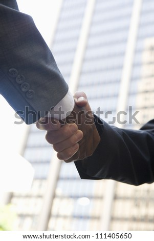 Low angle view of business people shaking hands