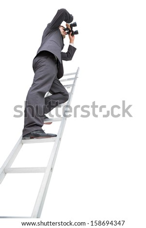 Low angle view of businessman standing on ladder using binoculars against white background