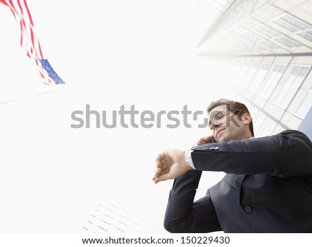 Low angle view of businessman using mobile phone while looking at wristwatch against buildings #150229430