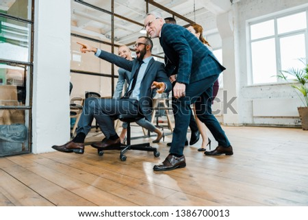 low angle view of cheerful businessman sitting on chair and pointing with finger near multicultural coworkers