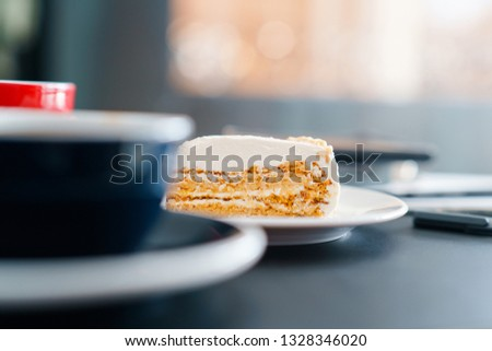 Low angle view of cheesecake and dark blue cup of coffee