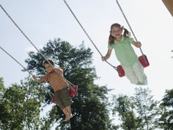 Low angle view of children playing on swings