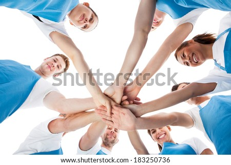 Low angle view of cleaners stacking hands over white background