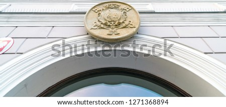 Low angle view of coat of arms on wall of the exterior of the Town Hall (former Men's Primary School) in Wadowice, Poland.  #1271368894