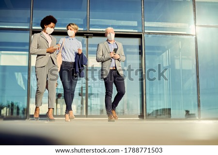 Low angle view of colleagues wearing protective face masks while leaving office building and communicating. Copy space.