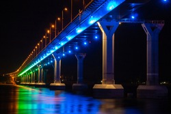 Low angle view of colourful bridge illuminated with different color lights at the night. Bridge stands on Volga river in Russia. Multi-colored light is reflected in the water.