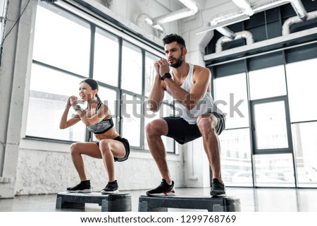 low angle view of concentrated sportive young couple in sportswear training with step platforms in gym
