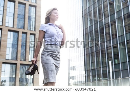 Low angle view of confident businesswoman holding high heels while standing outside office buildings #600347021