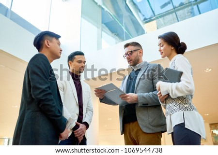 Low angle view of confident young entrepreneur conducting negotiations with business partners while gathered together at spacious open plan office, pretty subordinate assisting him