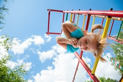 Low angle view of cute blond girl wearing blue tshirt hanging from a monkey bars. Girl is smiling with her eyes closed. Blue summer sky with clouds and tree leaves are seen in the background.
