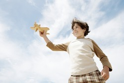 Low angle view of cute elementary boy flying toy airplane against cloudy sky