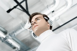 Low angle view of cyborg in eye lens and headphones looking away
