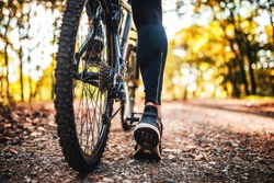 Low angle view of cyclist riding mountain bike on rocky trail at sunset. Focus on right leg.