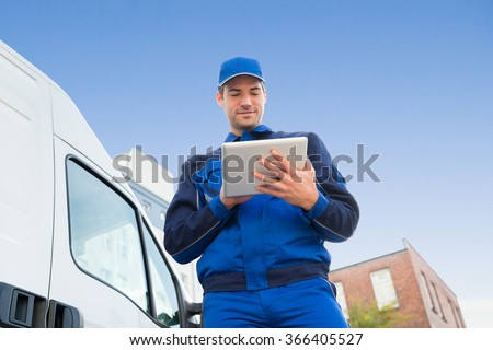 Low angle view of delivery man using digital tablet by truck against sky #366405527